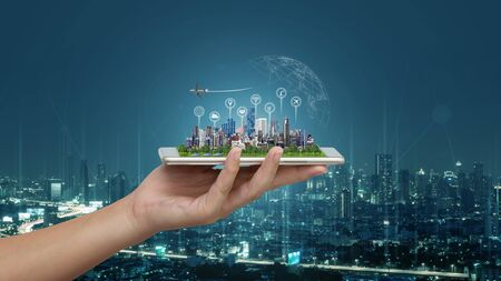Smart city and Internet of things (IOT) on smartphone in hand, objects icon connecting together, Internet networking concept with background modern city blurred. Banque d'images