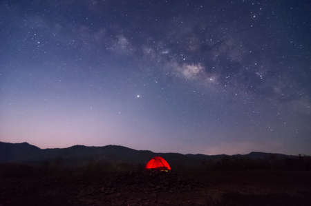 Red tent in reservoir under Milky way galaxy with stars and space dust in the universe, long speed exposure with noise. Baan Sop pat, Mae Moh Lampang Thailand. Stock Photo