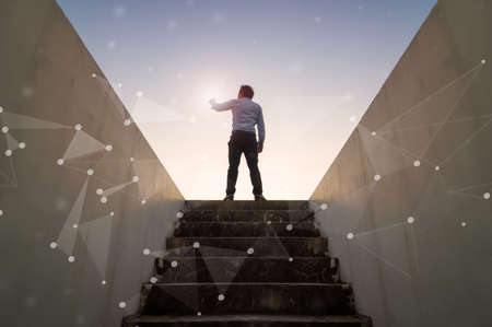 Businessman climbed on top of the stairs going to the city,  Ambitions concept and Success business with abstract network technology. Stock Photo