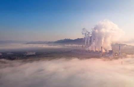 Aerial view steam fumes above the coal power plant in large area The machine is working to generate electricity the morning with fog and clouds. Stock Photo