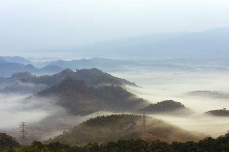 fog on mountain mae moh lampang with High voltage power transmission towers.