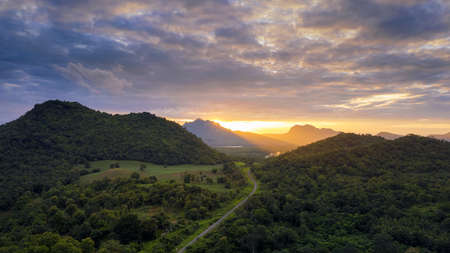Beautiful Aerial view sunset over the mountain range at the north of thailand, Beauty green forest landscape with railway below.
