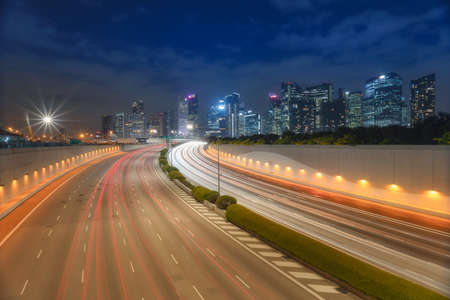 Singapore busy road and city background during rush hour with motion-blurred vehicle, car in Singapore city highway. 写真素材