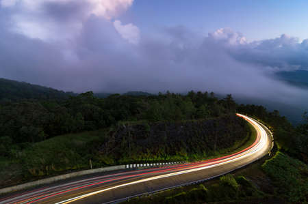 Beautiful road on the way up to Inthanon National Park at dusk, fog in the forest.