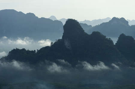 Landscape of mountains covered with fog and green trees at morning time Khao Thalu Chompon. Stock Photo