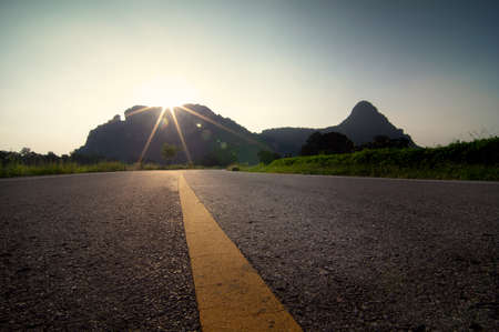 Beautiful road in the mountain valley with warm evening illumination. Stock Photo