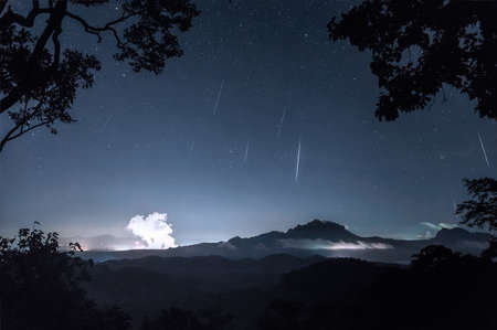 Geminids meteor shower in the night sky with the mist on hill, Long Exposure, Mae Moh Lampang Thailand.