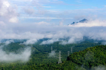 High voltage power transmission towers in fog on mountain mae moh lampang. 写真素材