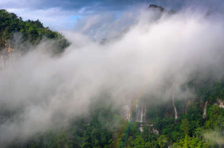 Fog and Rainbow in front of Thi Lo Su Waterfall, Beautiful waterfall in deep forest, Umphang National Park, Tak Province, Thailand. 写真素材