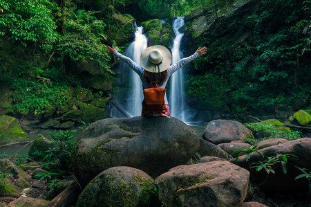 Rear view of young woman in front of Sapan Waterfall, Khun Nan National Park, Boklua District, Nan Province, Thailand. 写真素材