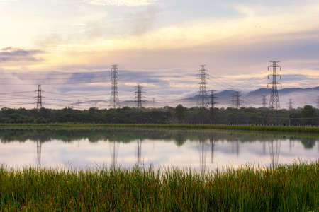 High-voltage transmission towers on the hill with reflection in the morning tranquil Mae Moh Lampang.