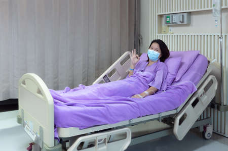 Young Asian female patient is smiling and showing ok gesture. Patient feels happy and comfortable with treatment and therapy on hospital bed in hospital room. Medical healthcare concept. 写真素材