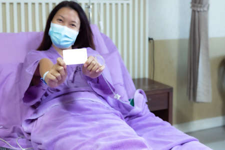 Young Asian female patient is smiling and showing blank credit card, Patient feels happy and comfortable with treatment and therapy on hospital bed in hospital room. Healthcare and Insurance concept. 写真素材