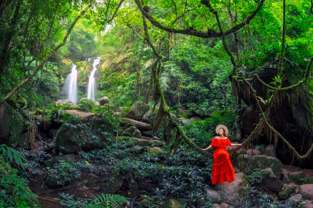 Beautiful woman in red dress sitting on the vine in front of the Sapan Waterfall, Khun Nan National Park, Boklua District, Nan Province, Thailand. 写真素材