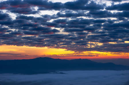 Beautiful fog over green forest on mountain with vivid sky, Aerial view sunrise over the mountain range at the north of thailand, Beauty rainforest landscape with fog in morning.