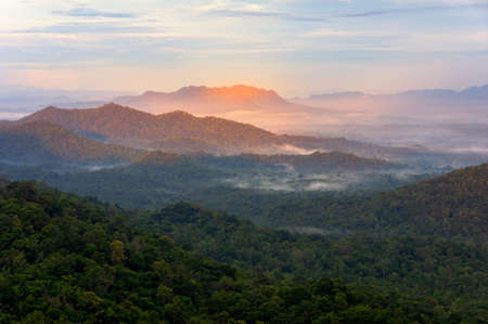 Beautiful mist over green forest on mountain, Aerial view sunrise beam red spot over the mountain range at the north of thailand, Beauty rainforest landscape with fog in morning.