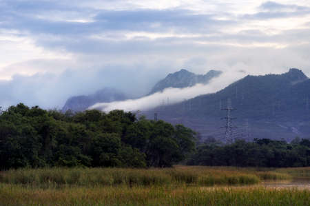 High voltage transmission towers on a hill In the morning light, mist is flowing on Khao Mae Mo, Lampang. 写真素材