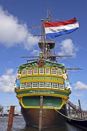 VOC ship in Amsterdam harbor the Netherlands with the dutch national flag   Stock Photo