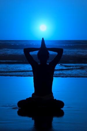 Yoga in de nacht op het strand bij volle maan weerspiegelt