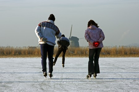 winterday: Ice skating on a cold winterday in the countryside on a frozen lake in the Netherlands   Stock Photo