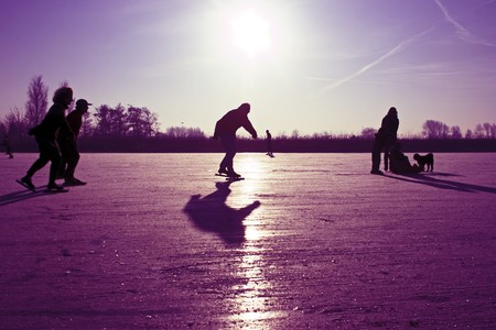 Ice skating at sunset in the Netherlands Stock Photo