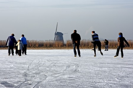 Ice skating on a cold winterday on a frozen lake in the Netherlands   Stock Photo