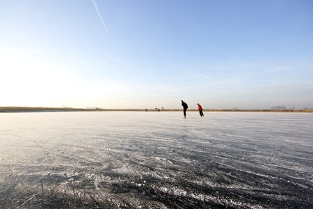 winterday: Ice skating on a cold winterday on a frozen lake in the Netherlands   Stock Photo