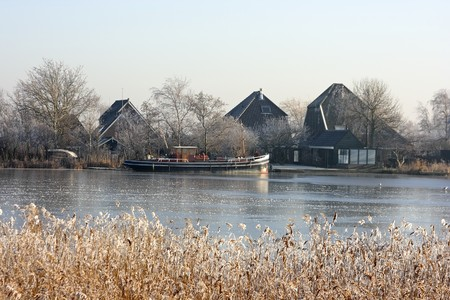 winterday: Cold winterday in Holland with frozen boat in a frozen icy canal in the countryside Stock Photo