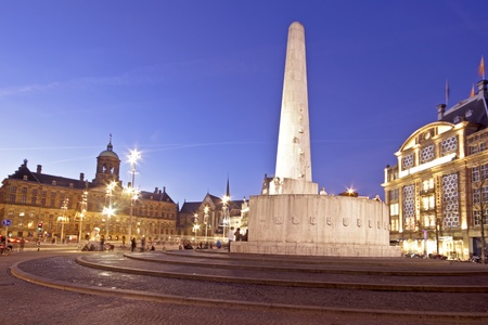 stoneworks: The National Monument on the Dam and in the background the Royal Palace in Amsterdam the Netherlands at twilight