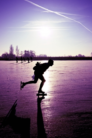 typically dutch: Ice skater at sunset on frozen ice in the fields of the Netherlands Stock Photo