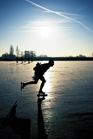 Schaatser bij zonsondergang op bevroren ijs op het gebied van Nederland