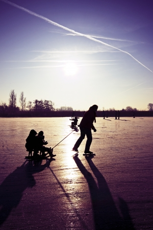 typically dutch: Sledging and ice skating at sunset on frozen ice in the fields of the Netherlands