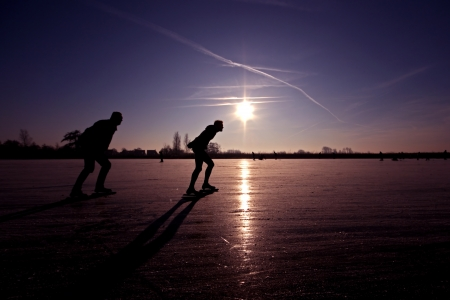 typically dutch: Ice skaters at sunset on frozen ice in the fields of the Netherlands