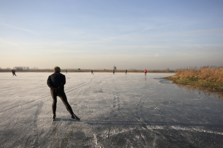 typically dutch: Typically dutch  ice skating on a frozen lake  on a cold winterday in the Netherlands