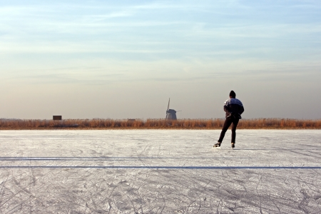 typically dutch: Typically dutch  ice skating on a frozen lake with view on a windmill on a cold winterday