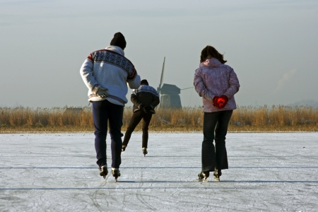 Typically dutch  ice skating on a frozen lake with view on a windmill on a cold winterday  photo