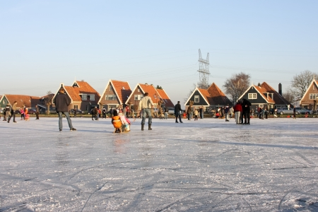 Typically dutch  ice skating on a frozen lake in the countryside from the Netherlands