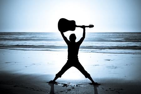 Gitarrist auf dem Strand bei Nacht Standard-Bild - 12234477
