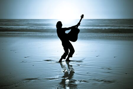 Guitar player on the beach at night