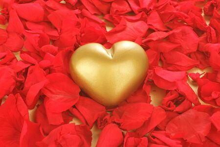 Golden heart on a bed of rose petals  photo