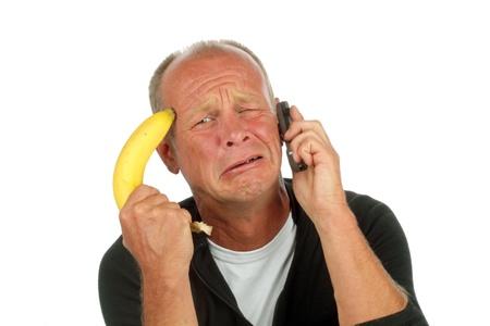 Desperate man pointing his banana gun against his head while phoning