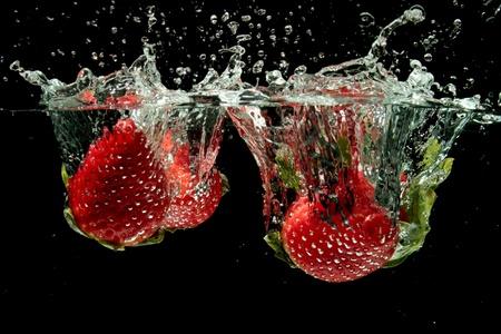 Aardbeien spatten in het water Stockfoto