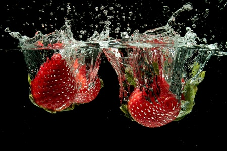 Strawberries splashing into water  Stock Photo