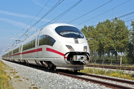 Fast speed train running in the countryside from the Netherlands 免版税图像