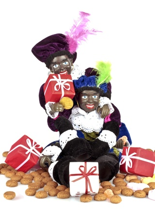gingernuts: Traditional dutch culture  Two black Piet with a bag full of gingernuts, candies and presents at 5th december