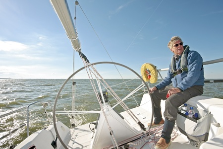 sailor man: Sailing on the IJsselmeer in the Netherlands on a beautiful sunny day  Stock Photo