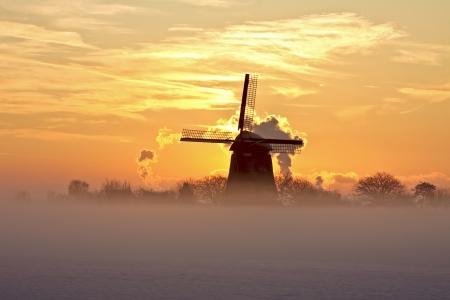 molino: Molino de viento de Traditonal en la niebla y la nieve en el crepúsculo en los Países Bajos Foto de archivo