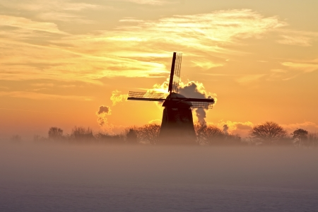 Traditonal windmill in fog and snow at twilight in the Netherlands Stock Photo