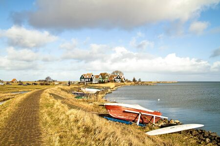 typically dutch: Wide view at the IJsselmeer with traditional houses in the Netherlands
