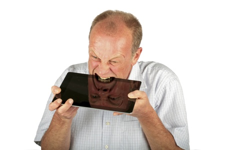 consuming: Angry man is consuming his tablet computer Stock Photo